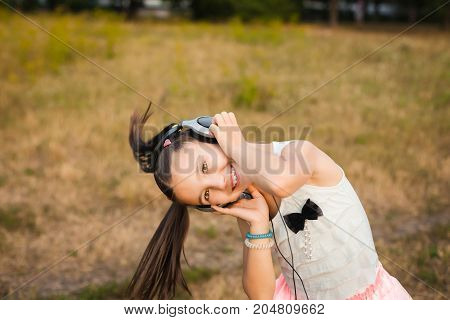 active girl twisting her head and waving her hair outdoor, healthy child with black and silver headphone dancing on meadow