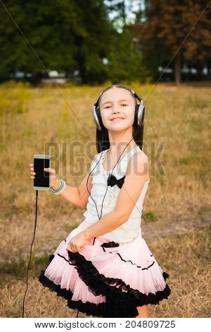 musical girl dancing in yard, pretty little woman listening music and smiling in white blouse and pink fluffy skirt