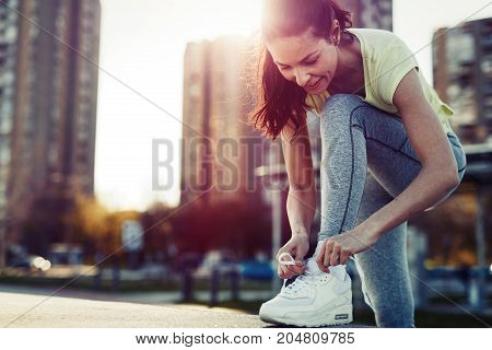 Attractive young sportswoman tying shoelace and getting ready for fitness