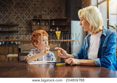Knowledge is power. Mindful senior woman talking to her grandson while both sitting at a dinner table and drawing together at home.