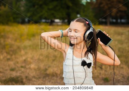 active girl with closed eyes having nice weekend outdoor, little girl with black and silver headphone listening song with pleasure