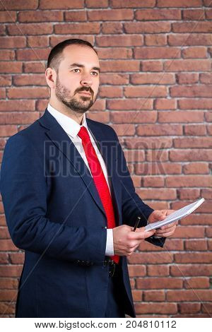 Businessman in a blue jacket with a notepad is going to write down with a black pen
