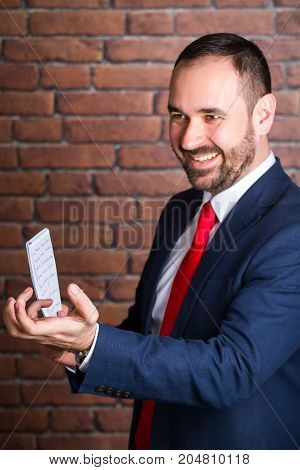 A businessman in a blue jacket with a notepad smiles and beckons to himself with his hand