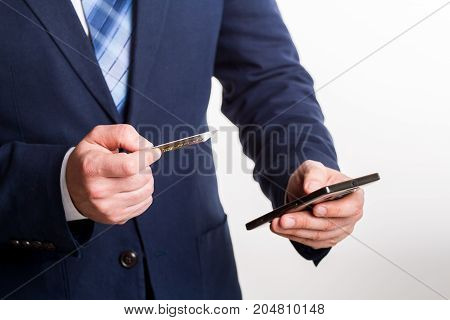 businessman in blue suit enters credit card information into phone