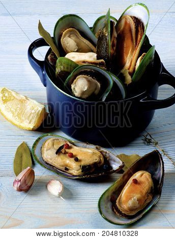 Arrangement of Fresh Boiled Green Mussels with Spices and Lemon in Dark Pannikin closeup on Blue Wooden background