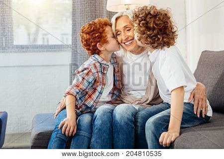 Tender moment. Loving senior woman embracing her grandchildren with a cheerful smile on her face while mindful grandsons kissing her.