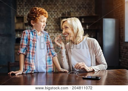 Dont you mind. Radiant elderly lady looking at her redhead grandchild and grinning broadly while putting an earphone n her ear for listening to the music playing.