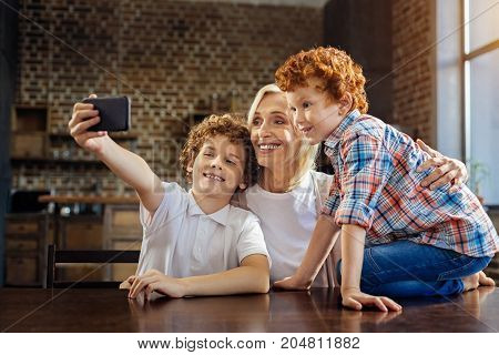 Memorable moment. Side view on a happy family members meeting at a dinner table and grinning broadly while taking a self portrait picture on a smartphone.