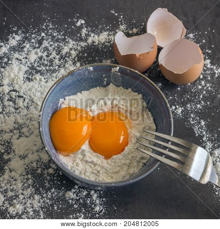 Eggs and flour in the blue bowl. Ingredients for home baking. Delicious Breakfast.