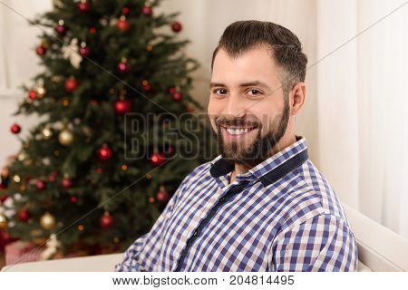 portrait of handsome bearded man smiling at camera at christmastime