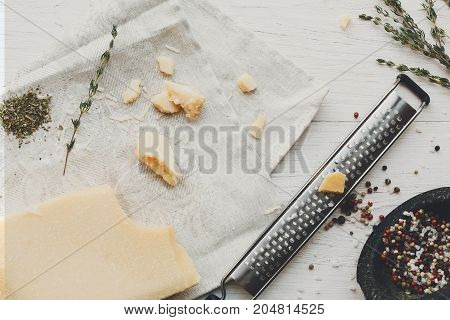 Parmesan piece closeup with small grater and various herbs and seasoning, rosemary and pepper. Classic italian cuisine cooking ingredients, grated hard cheese. Top view, flat lay