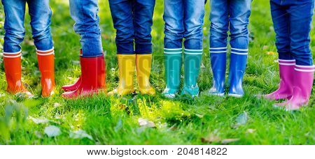 Little kids, boys and girls in colorful rain boots. Close-up of children in different rubber boots, jeans and jackets. Footwear for rainy fall.
