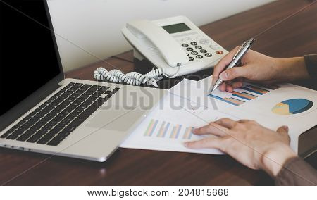 Close up businessman analyzing graph document with laptop and telephone.