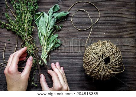 thyme and sage on wooden background with hands top view.