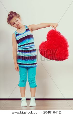 Funny little girl putting red soft heart shape pillow aside. Adorable cute kid with sign symbol of love.
