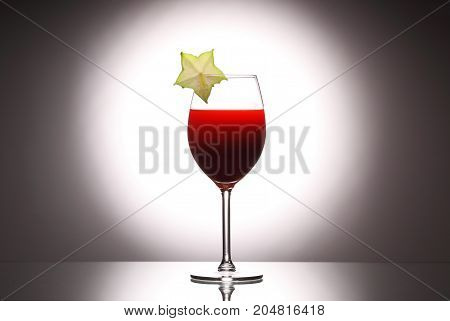 Wineglass Red Liquid Cocktail Decorated With Green Carambola On Studio Background.