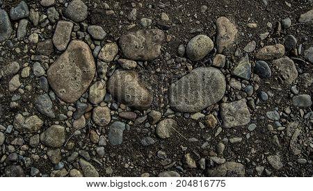 Rocky soil background. Stony soil. Stony ground. Rocky ground. Grunge rocky soil background.