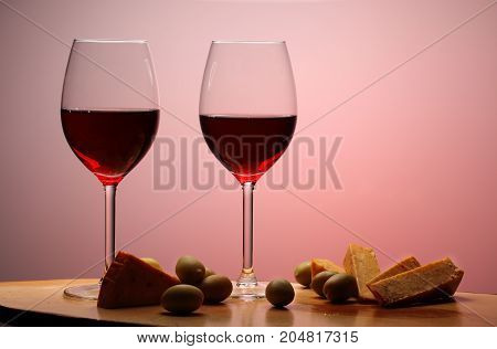 Wineglasses With Red Wine On Wood With Cheese And Green Olives. Studio Background.