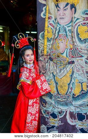 Chachoengsao, Thailand - July 14, 2013 : Beautiful woman with traditional chinese red dress at Chinese shrine door with painting of ancient soldier in Thailand.