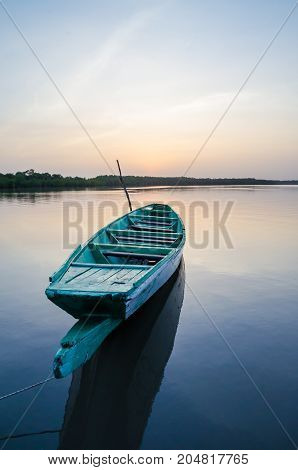 Beautiful wooden fishing boat in Gambia river during blue hour in the evening, The Gambia, West Africa.