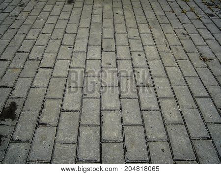 Paving slabs. Pavement tile.Sidewalk tile. Gray paving tile background. Grunge paving background.