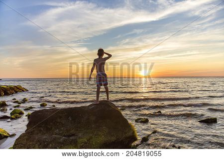 boy on a rock by the sea gazes into the distance. child looking at the sea at sunset