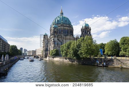 Berlin Cathedral across the Spree River in Germany on a partly cloudy summer day