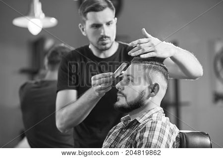 Black and white shot of a professional barber working cutting hair of his client with scissors.