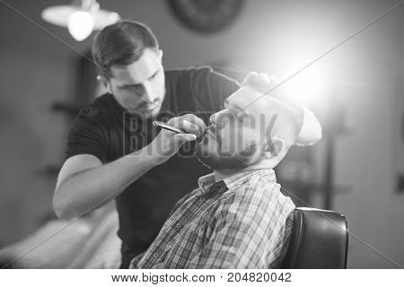 Monochrome shot of a handsome young bearded man getting his beard shaved and trimmed at the local barbershop.