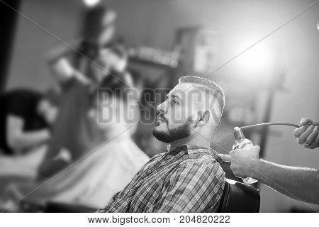 Monochrome shot of a young bearded man being sprayed with cologne after shaving at the local barbershop.