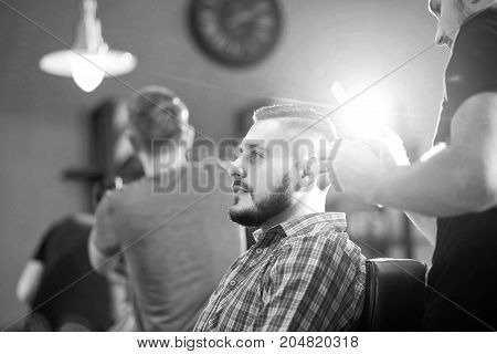 Monochrome shot of a young attractive bearded man smiling while getting a new haircut by his barber.