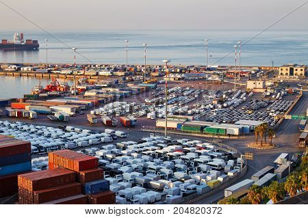 Port terminal with containers new cars and wagons in the early morning