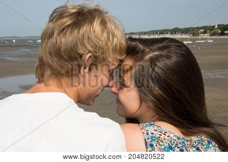 Happy Young Woman Kissing Her Handsome Boyfriend In Summer Vacation On Beach, Lifestyle Portrait Of