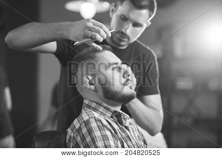 Monochrome shot of a young handsome man getting a haircut by professional barber at the barbershop.