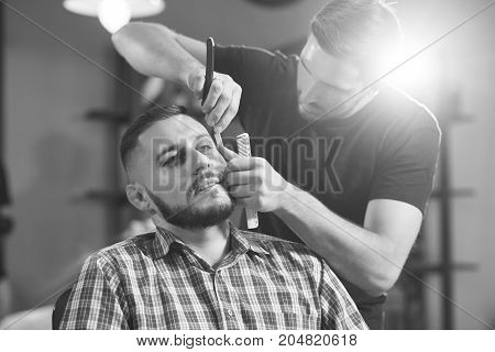 Monochrome shot of a bearded young handsome man at the barbershop.