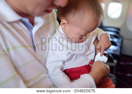 Asian Father / Parent holding & put baby seat belt on Little Asian 18 months / 1 year old toddler baby boy child on flight Safety of Infants and Children on Board Taking children on a plane concept