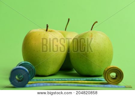 Sports And Healthy Lifestyle Symbols. Apples Near Rolled Measuring Tapes