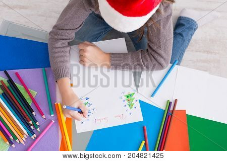 Writing letter to santa. Child in santa hats make wish list of presents for christmas. Winter holidays. Girl drawing, top view