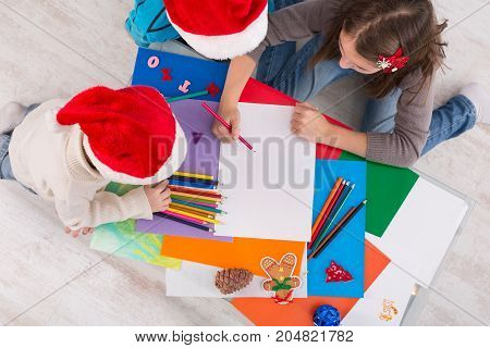 Writing letter to santa. Children in santa hats make wish list of presents for christmas. Winter holidays. Boys and girl, brothers and sister draw, top view, copy space on sheet of paper