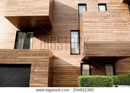 Modern contemporary wood sided building with balconies and windows