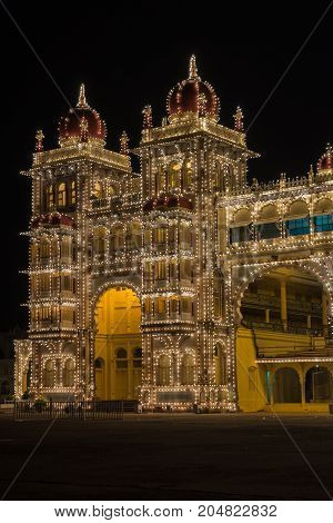 Mysore India - October 27 2013: Southeast corner towers of Mysore Palace at nightly Sound and Light show. Beige building with towers and maroon domes. Hundreds of lights.