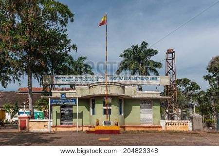 Mysore India - October 28 2013: Green entrance guard building with State red and yellow flag of historic Karnataka Soap and Detergents factory under blue sky and with green trees .