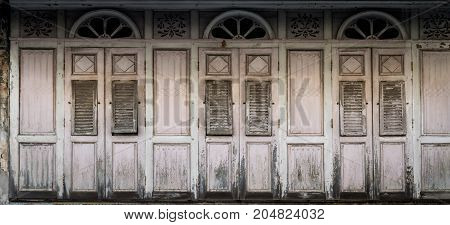 Closed old shuttered weathered wooden window in the Songkhla province Thailand