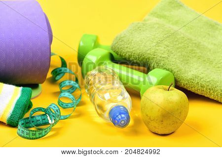 Barbells, Apple, Towel, Measuring Tape And Water Bottle Near Mat