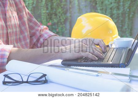 Architect engineer using laptop for working with white helmet laptop and coffee cup on table.