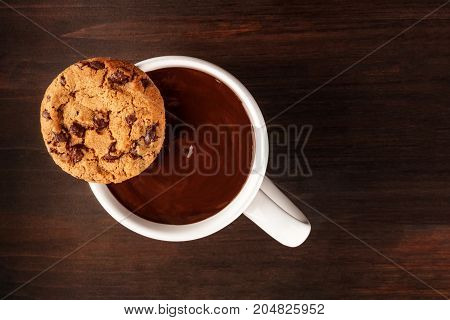 An overhead photo of a chocolate chips cookie on top of a mug of hot chocolate, shot from above on a dark rustic background with a place for text