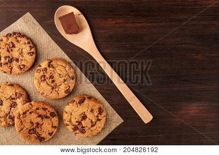An overhead photo of chocolate chips cookies, shot from above on a piece of baking paper, with a wooden ladle, an ounce of chocolate, and copy space