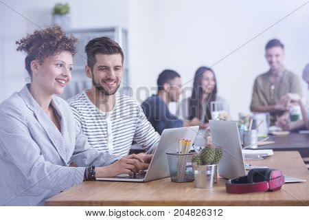 Couple of young workers sitting with laptop and making project together