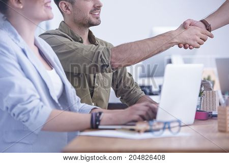 Young intern in khaki shirt giving handshake to his client at the office