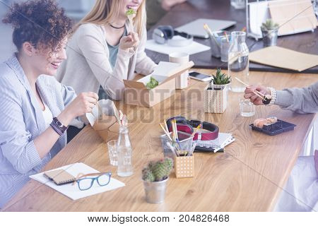 People eating lunch by wooden desk with office supplies and headphones